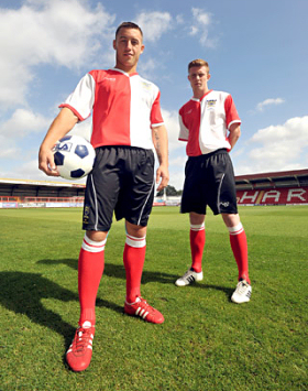 Lee Vaughan and Jack Byrne modelling the special shirts to celebrate 125 years of Kidderminster Harriers